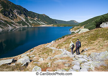Trekking in mountains - Couple trekking by the side of...