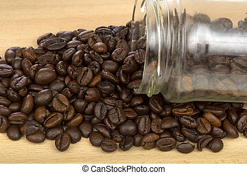 Coffee beans in a bottle on wood background