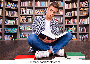 Doing his research in library. Concentrated young man reading book while sitting against bookshelf