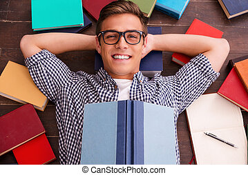 Reading is my hobby! Top view of happy young man holding hands behind head and smiling while lying on the hardwood floor with colorful books laying all around him
