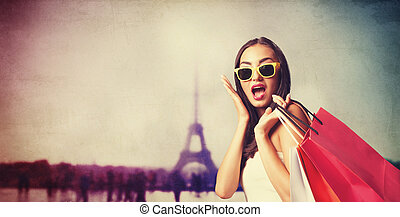 Brunette girl with shopping bags on Parisian background