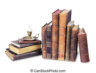 Old books and candle in a candlestick on a white background