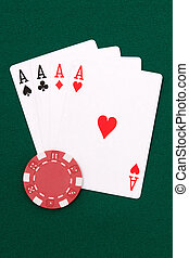 Four aces and red chip on green linen
