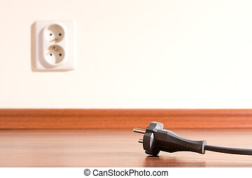 Unplugged - Two pin plug on the floor and electrical outlet...