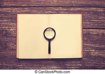 opened book and loupe on a table