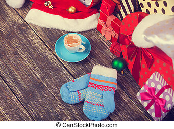Cup of coffee with heart shape, mittens and christmas gifts.