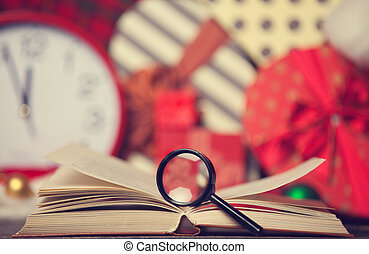 Loupe and book on christmas gifts background