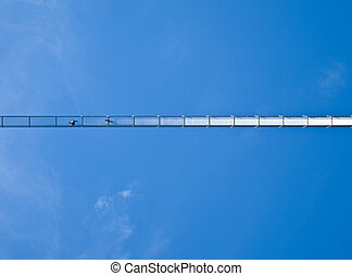 swing bridge from below - two people walking over a swing...