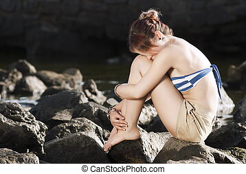 Lonely Woman Sitting On Rock - Portrait Of Depressed Young...