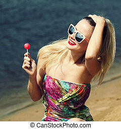 Young sexy woman  holding lollipop on water background. Outdoors, lifestyle.