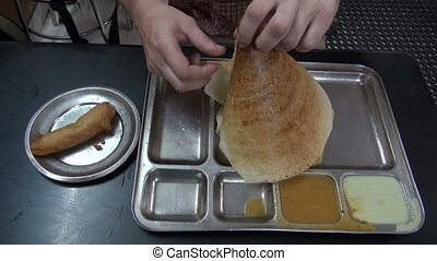 tourist eating exotic food dosa in South india restaurant
