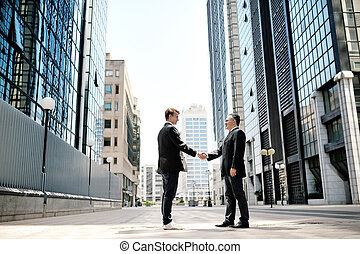two businessmen shaking hands on background office corporate...