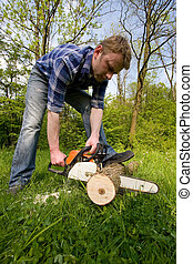 Young men is cutting wood by chain saw