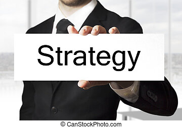 businessman holding sign strategy - businessman in black...