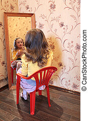 girl makes up her face before a mirror - litte girl makes up...