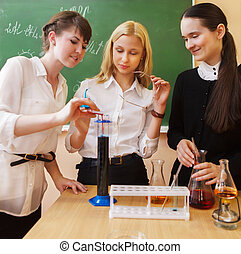 Girls working in chemistry laboratory at the classroom -...