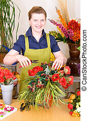 Young Florist in shop preparing flower decoration