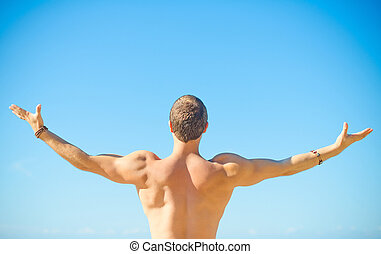 Muscular attractive man near the sea Freedom concept