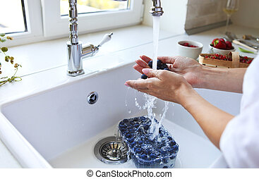 Woman washing blueberry, strawberry and red currant at home...
