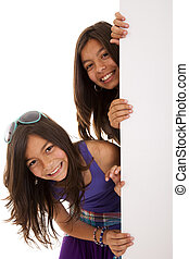 sisters holding a blank billboard - young beautiful sisters...