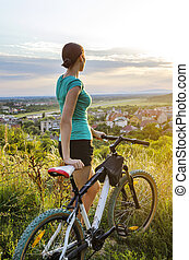 Moutain bike woman looking at the sunset standing on a hill