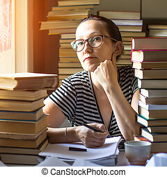Woman writes on a notebook in a room with lots of books (loking at the camera)