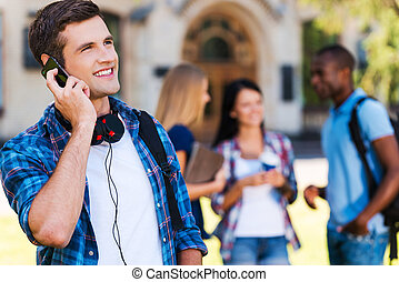 Talking with friends. Handsome young man talking on the mobile phone and smiling while standing against university building with his friends chatting in the background