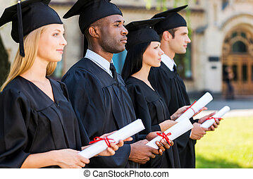 Looking to a bright future Four college graduates holding...