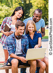 Surfing web together Four happy young people discussing...