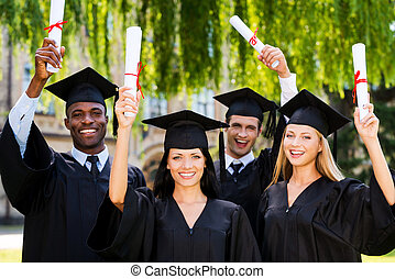 Happy graduates Four college graduates showing their...