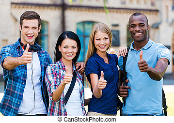 We love studying! Four happy young people showing their thumbs up and smiling while standing close to each other outdoors