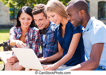 Surfing the net together. Four happy young people looking at...