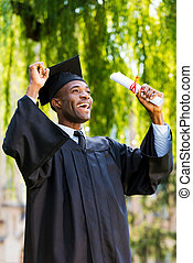 Finally graduated! Happy young African man in graduation...