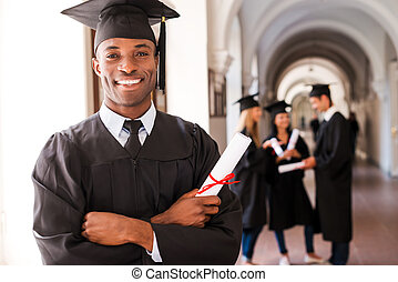 Confident graduate Happy African man in graduation gowns...