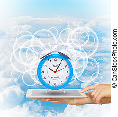 Hands hold tablet pc with alarm clock. Blue sky background