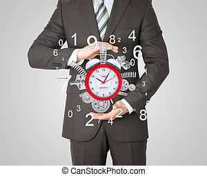 Businessman hold alarm clock with springs and gears. Gray...