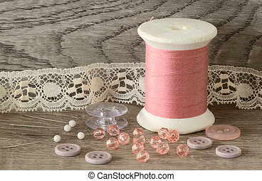 Close up of pink cotton threads spools, bids, and buttons on wooden surface and background
