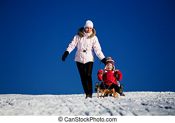 sledding - winter activities. A mother and daughter sledding...