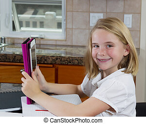 Pretty young girl doing her homework in the kitchen