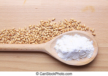 Wheat and flour on wooden background