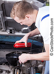 Mechanic changing car oil - Young mechanic changing car oil...