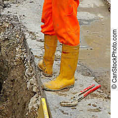 construction worker with boots and a spanner in roadworks