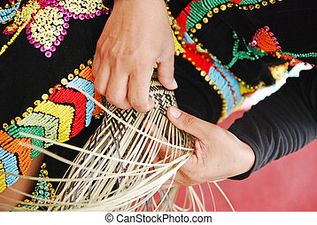 Weaving - A hand showing the activity of weaving a bamboo...