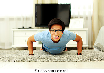 Portrait of a smiling  young man doing push ups in the living room at home