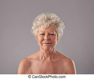 Attractive senior woman with her eyes closed in thought -...