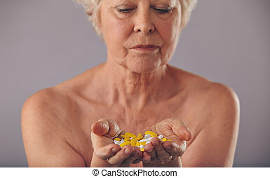 Medication to stay young - Closeup image of a mature woman...