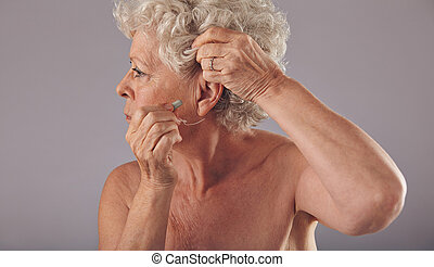 Senior woman wearing a hearing aid - Side view portrait of a...
