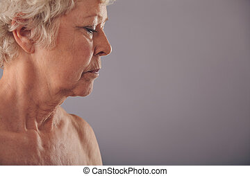 Profile view of senior woman face against grey background,...