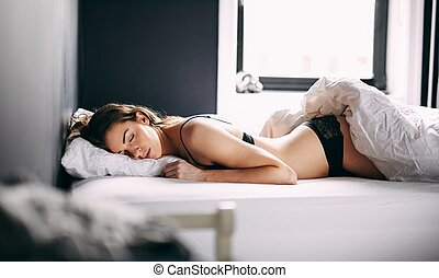 Female model sleeping on her bed - Young caucasian woman in...