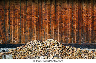 Choped firewoods near wooden wall